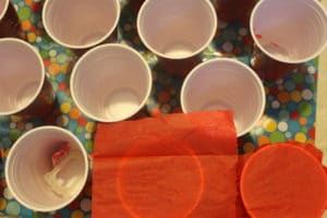 Fill the cups with a few treats. Cut tissue paper in squares and rubber band the tissue around the top of the cup.