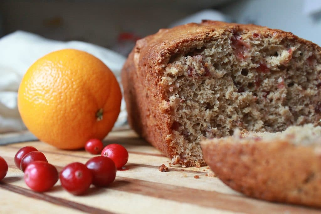Cranberry Orange Bread with cranberries and an orange